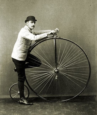 man standing with a penny farthing bicycle from the 1880s