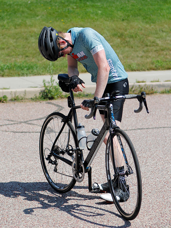 A man in an IRONMAN cycling jersey hangs his head in exhaustion while resting his arm on his bike sadsle