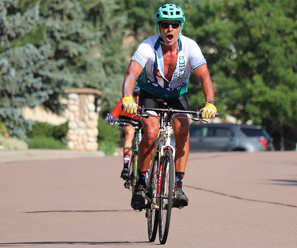 A man riding a mountain bike down a road with his mouth open in joy